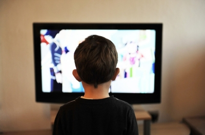 Photo shows the head and shoulders of a small child from behind, watching television. The child's head is centred on the television screen.