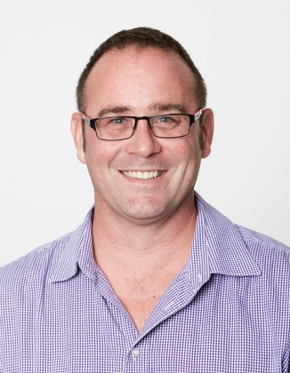 Head and shoulders portrait of Justin, who has a high hairline, very short hair, glasses, open-necked buttoned shirt and is smiling.