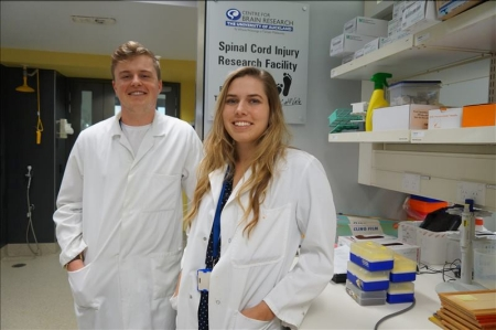 Connor and Laverne wearing lab coats, in a laboratory.